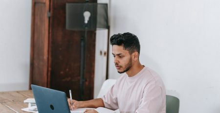 man at his computer works on getting late invoices paid
